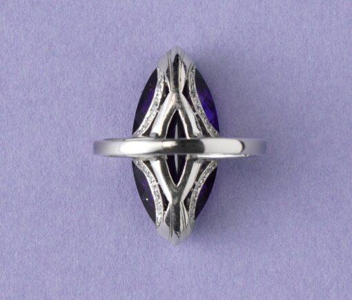 (136)Een platina ring met een navette geslepen, prachtige amethyst aan de zijkanten van de setting vier boogjes waarin 7 kleine diamantjes op een rij gezet. Op de scheen twee baguettes in de lengte gezet. (totaal circa 0.62 karaat). ringmaat: 17 + mm. 6 ¾ US. gewicht: 6.35 gram. afmetingen amethist: 2.2 x 1 cm.  breedte scheen: 1.8 – 2 mm.